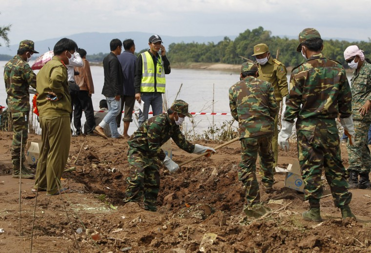 Soldiers survey the crash site of an ATR-72 turboprop plane in Laos. (REUTERS/Chaiwat Subprasom )