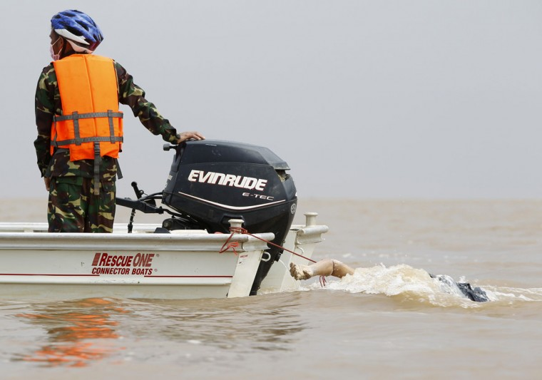 A soldier operates a rescue boat, used to pull the dead body of a victim retrieved from the crash site of a Lao Airlines ATR-72 turboprop plane in the Mekong river. (REUTERS/Chaiwat Subprasom)
