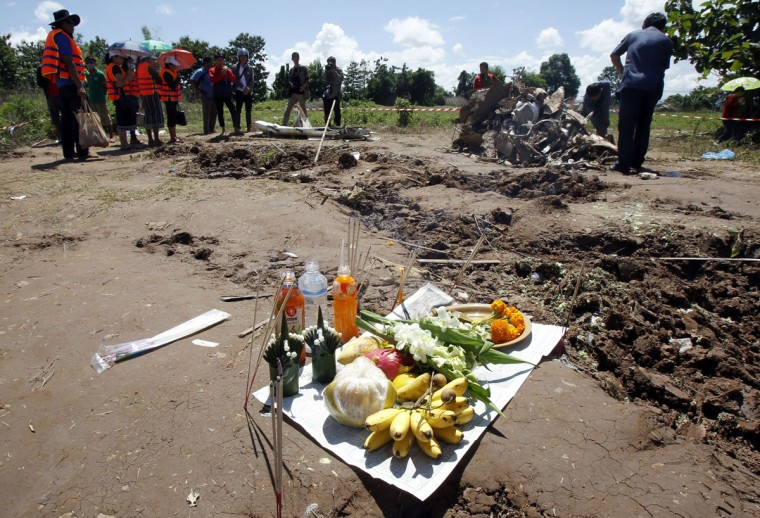 Offerings left by villagers and relatives of the victims of a Lao Airlines ATR-72 turboprop plane crash, are seen as people walk at the crash site near the Mekong river. (REUTERS/Chaiwat Subprasom)