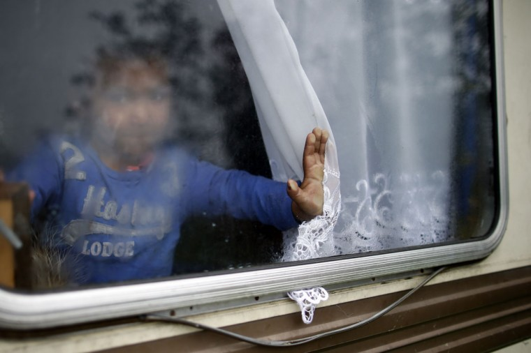 A Roma child is seen at a window of a caravan at an encampment of Roma families in Triel-sur-Seine, near Paris, October 18, 2013. At this encampment of migrants from Romania, one of the approximately 400 such camps spread throughout France, people say they want to work in France and become integrated, because they have no prospects in Romania. (Benoit Tesser/Reuters)