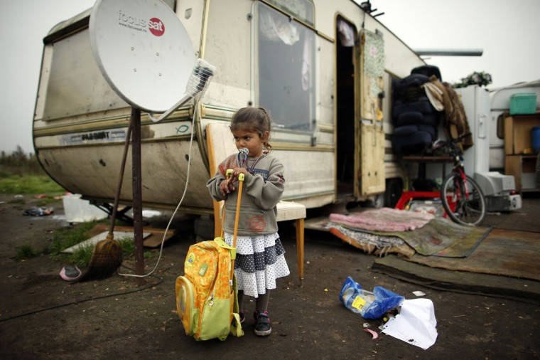 A girl leans on a school back pack outside a caravan at an encampment of Roma families in Triel-sur-Seine, near Paris, October 18, 2013. At this encampment of migrants from Romania, one of the approximately 400 such camps spread throughout France, people say they want to work in France and become integrated, because they have no prospects in Romania. (Benoit Tesser/Reuters)