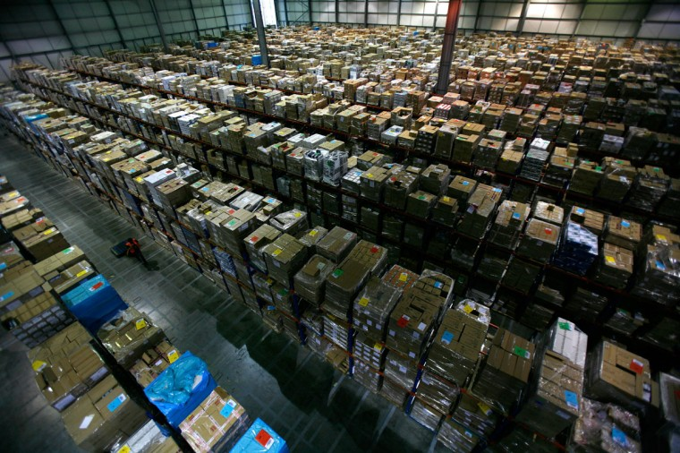 A worker carries boxes through the Amazon warehouse in Milton Keynes November 30, 2007. (Kieran Doherty/Reuters)