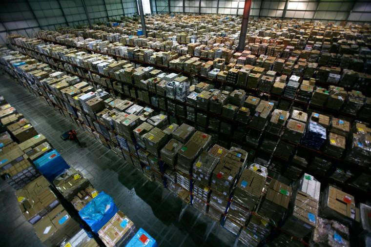 A worker carries boxes through the Amazon warehouse in Milton Keynes November 30, 2007. (Kieran Doherty/Reuters)