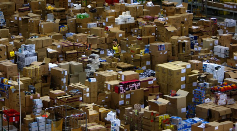 A worker walks through aisles at the Amazon warehouse in Milton Keynes November 30, 2007. (Kieran Doherty/Reuters)