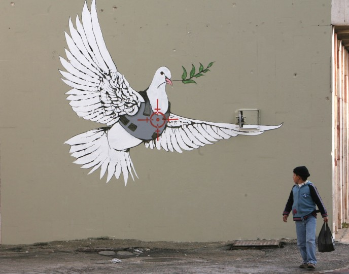 A Palestinian boy looks at one of six new images painted by British street artist Banksy as part of a Christmas exhibition in the West Bank town of Bethlehem on December 2, 2007. (REUTERS/Ammar Awad)