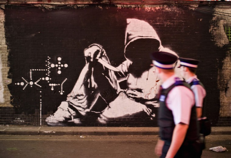 Policemen look at a mural by graffiti artist Banksy painted on the wall of a tunnel near Waterloo Station in London on June 23, 2008. (REUTERS/Finbarr O'Reilly)