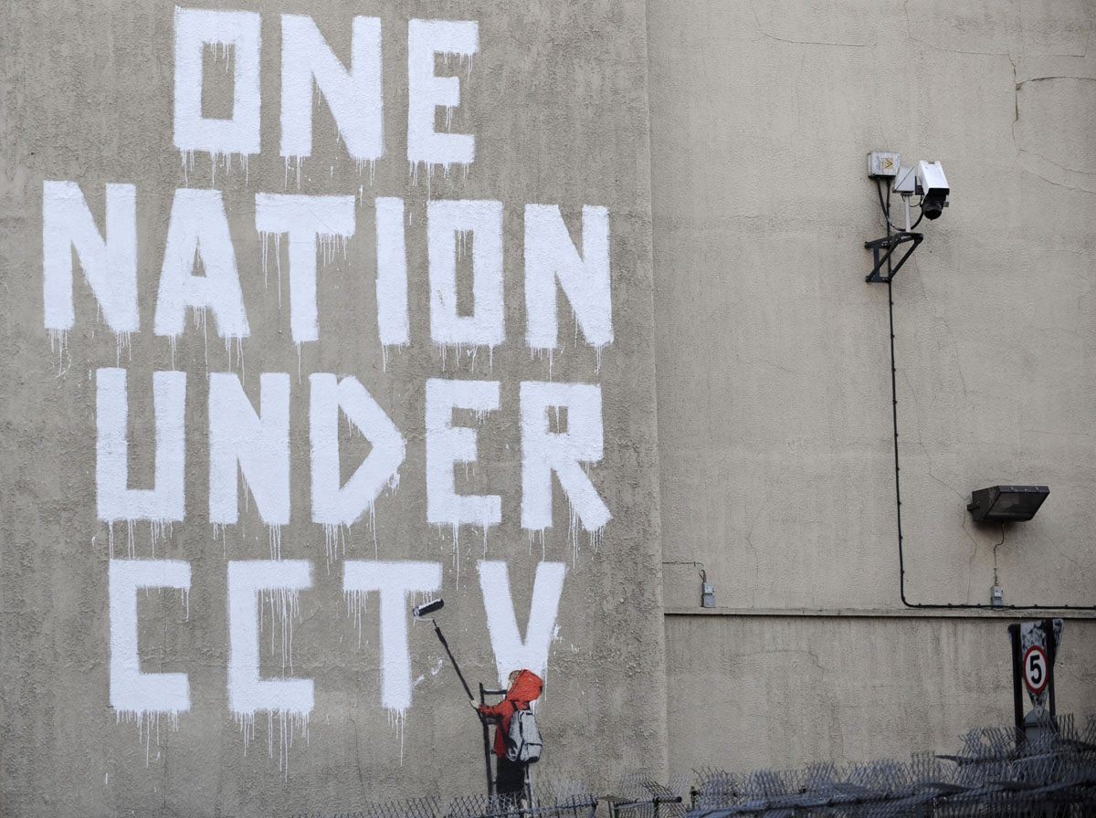 Street graffiti by elusive graffiti artist banksy is seen on a wall next to a cctv camera in central london on november 25 2008 reuters toby melville