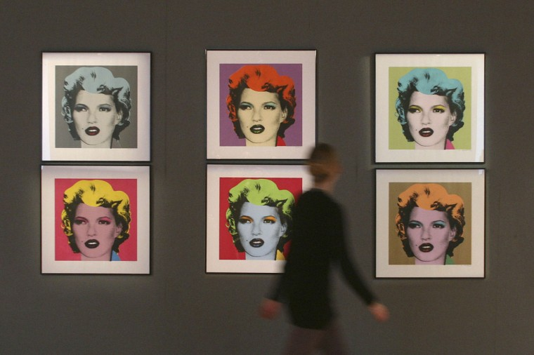 """A woman walks past a set of six prints entitled """"Kate Moss 2005"""" by British artist Banksy as she poses for photographers during a photocall for Bonhams' forthcoming Urban Art Sale, at Bonhams Auctioneers in London on February 19, 2009. (REUTERS/Andrew Parsons)"""