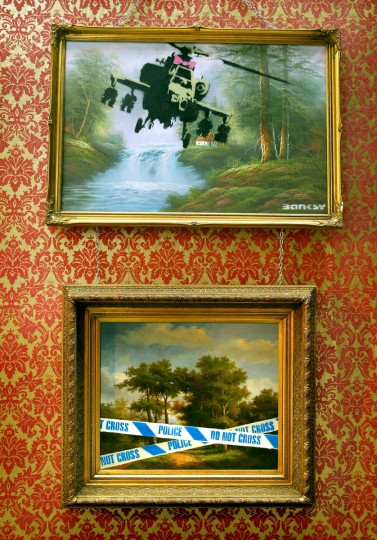 Vandalized classic oil paintings hang on display as part of the Turf War exhibition by graffiti artist 'Banksy' in London's East End on July 17, 2003. (Reuters photo)