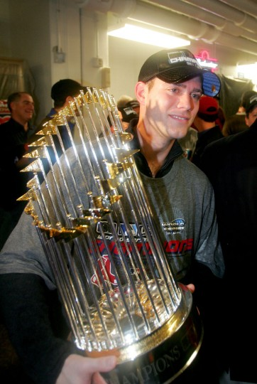 General manager Theo Epstein of the Boston Red Sox celebrates in the locker room with the Championship trophy after defeating the St. Louis Cardinals 3-0 in game four of the World Series on October 27, 2004 at Busch Stadium in St. Louis, Missouri. (Ezra Shaw/Getty Images)