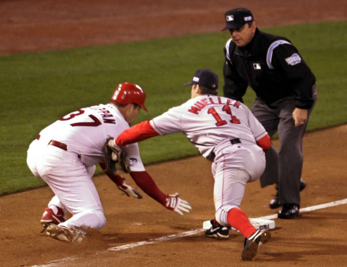 Third base umpire Gerry Davis watches as Boston Red Sox third baseman Bill Mueller tags out St. Louis Cardinals pitcher Jeff Suppan as he tries to get back to third base during the third inning of Game 3 of the World Series at Busch Stadium in St. Louis, Tuesday, Oct. 26, 2004. Cardinals' Larry Walker grounded out to second and Suppan was thrown out on a throw by first baseman David Ortiz. (Mark Humphrey/AP Photo)