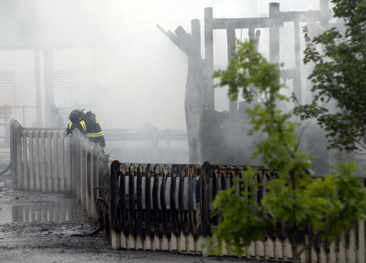 In September 2008 an exhausted firefighter leans against the playground fence where a fire destroyed a YMCA playground on 33rd Street and Ellerslie Avenue. (Barbara Haddock Taylor/Baltimore Sun)