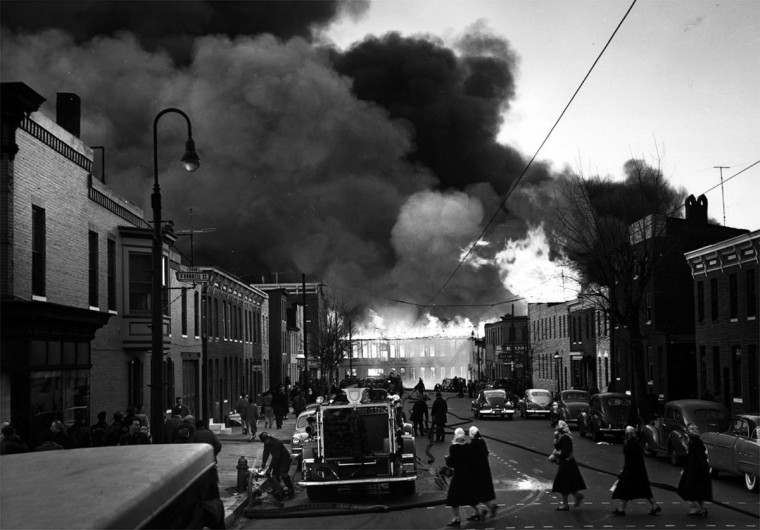 "Startled pedestrians look on and firemen prepare their equipment as fire engulfs a city street in Canton in Feb. 1953. This photo bore the title, ""The Start of 18 Alarms."" (Hans Marx/Baltimore Sun)"