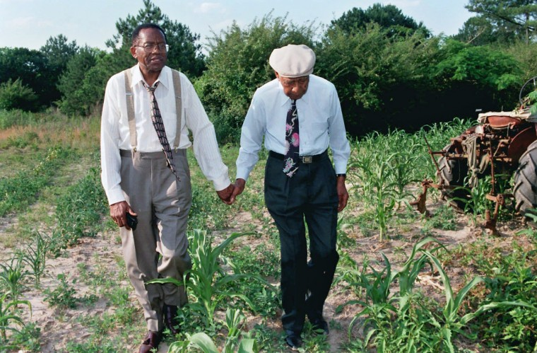 In May 1997 in Tuskegee, Alabama, Syphillis experiment survivor Herman Shaw, on right, walks on his land, hand in hand with his lawyer, Fred Gray, left. The tractor that's visible on the far right is a 1941 model that Mr. Shaw keeps running. (Barbara Haddock Taylor/Baltimore Sun)