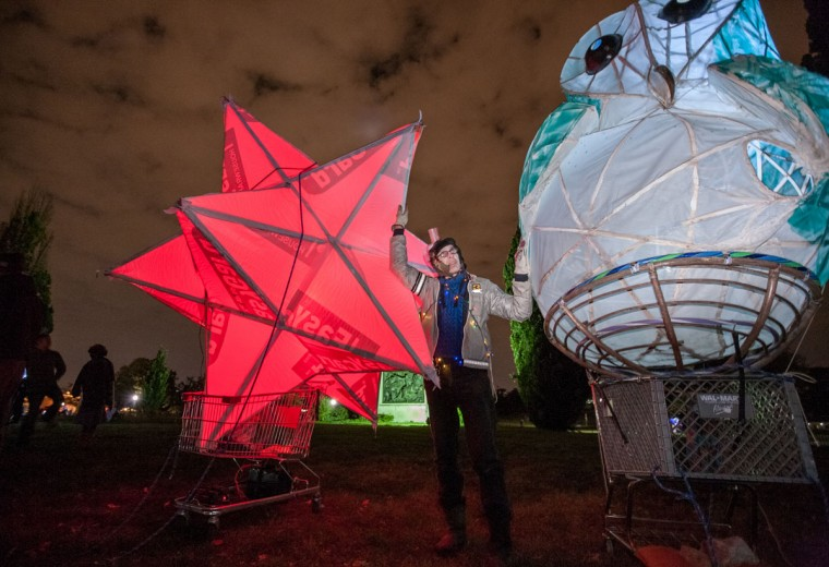 Daniel Van Allen, of Hollins Market, stands with his parade creations, a stellated dodecahedron, left, and an illuminated Barn Owl. The Great Halloween Lantern Parade was held October 26, featuring costumes, music, food trucks and other performances. (Nate Pesce/For the Baltimore Sun)
