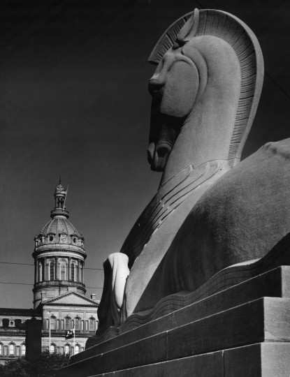 The Baltimore City Hall may be unique as a civic edifice -- it was constructed and furnished for less money than had been appropriated. The building is made of Baltimore County marble and has a cast iron dome. In the foreground is one of the horses which flank the entrance to the War Memorial. (A. Aubrey Bodine/1956 Baltimore Sun)