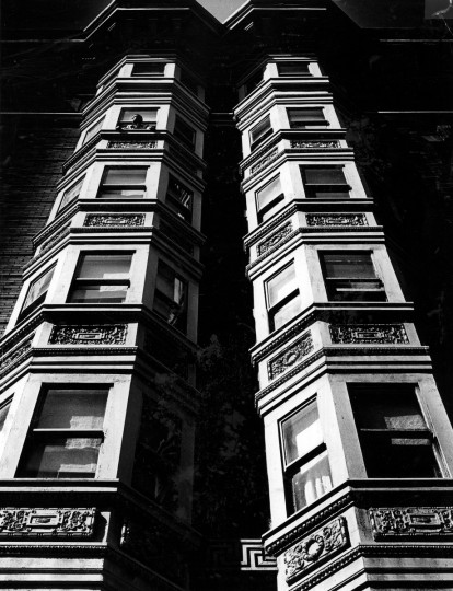 This photograph from May 1965 shows the play of light and shadow on a column of bay windows in downtown Baltimore. Near the top of the building, an early riser sticks his head out of a window to check the weather. (Robert F. Kniesche/Baltimore Sun)