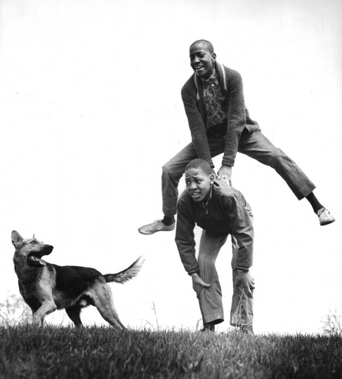 "As the warmer weather of spring arrives in Druid Hill Park in April 1962, Ralph Willett, 14, celebrates the occasion by leap-frogging over Barrington Wood, 13, as ""Duke"" runs alongside. (Ellis Malashuk/Baltimore Sun)"