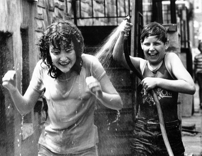 Carol Poole gets a good soaking, and doesn't mind at all, as William Webster Jr. sprays a hose on a hot day on Wyeth Street in Southwest Baltimore in 1981. (Walter M. McCardell/Baltimore Sun)