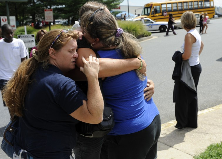 Robin Vitek, left, embraces her son Nick (center) and Cynthia Rose, right, embrace Nick Vitek, an 11th grader from Perry Hall Middle School. Parents waited for Perry Hall High School students to be released from school after a shooting on opening day of school in August 2012. (Barbara Haddock Taylor/Baltimore Sun)