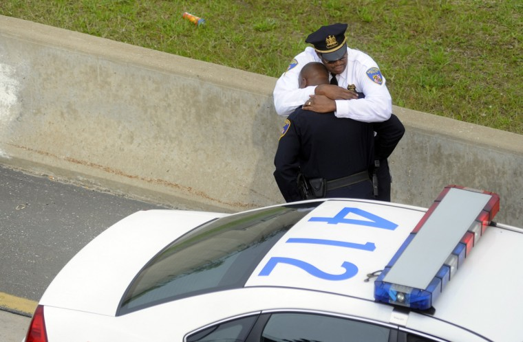 In October 2010, Baltimore city police officers comfort each other near the accident scene on route 40 eastbound in West Baltimore involving a fellow city police officer driving a police cruiser and a city fire engine. (Barbara Haddock Taylor/Baltimore Sun)