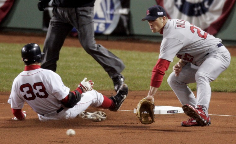 Boston Red Sox Jason Varitek, left, wins the race to the base for a triple against the St. Louis Cardinals and third baseman Scott Rolen in the first inning of game two of the World Series in Boston, Sunday, Oct. 24, 2004. (Amy Sancetta/AP Photo)
