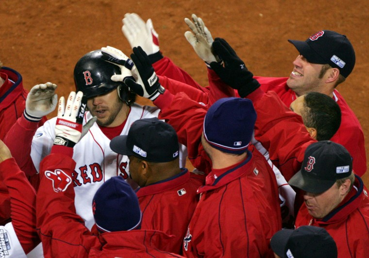 Boston Red Sox teammates mob Mark Bellhorn, left, after his 8th -inning, two-run home run against the St. Louis Cardinals in game one of the World Series in Boston, Saturday, Oct. 23, 2004. (Chitose Suzuki/AP Photo)