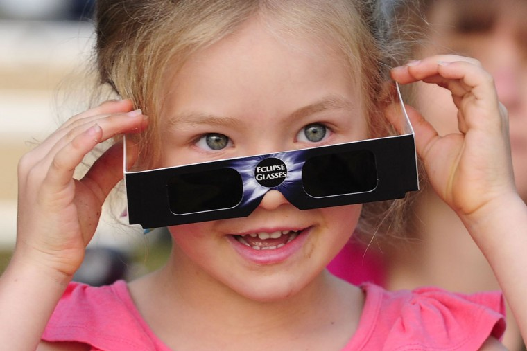 A young girl attempts to view the solar eclipse through special eclipse viewing glasses on November 14, 2012 in Palm Cove, Australia. Thousands of eclipse-watchers have gathered in part of North Queensland to enjoy the solar eclipse, the first in Australia in a decade. (Ian Hitchcock/Getty Images)