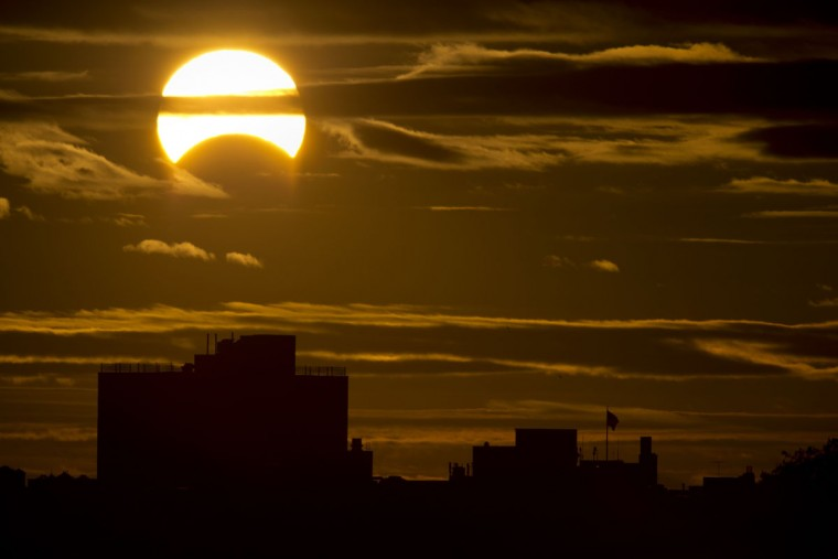 A partial Solar eclipse is seen just after sunrise over the Queens borough of New York across the East River on November 3, 2013 in New York. (Stan Honda/AFP Photo)