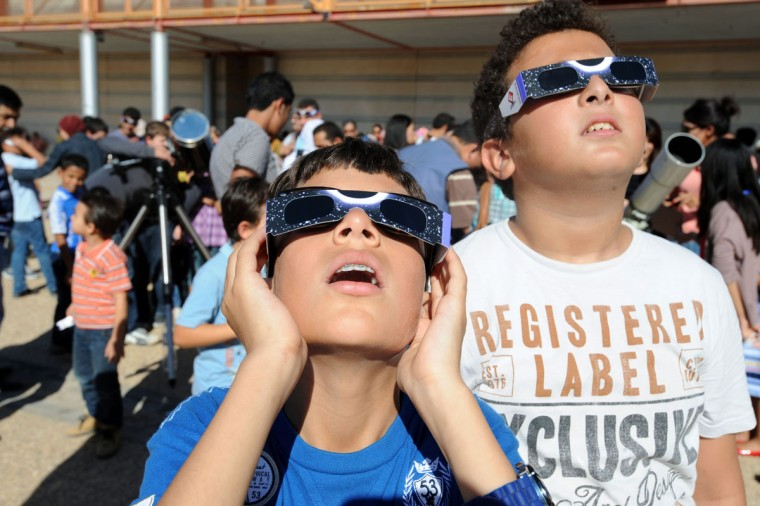Tunisian children wear protective glasses as they watch rare solar eclipse through a cloud covering in Tunis on November 3, 2013. A rare solar eclipse swept across parts of Africa, Europe and the United States as the moon blocks the sun either fully or partially, depending on the location. The width of the shadow of the eclipse was 58 km and the maximum duration of totality, the maximum time that the moon covered the sun completely. (Fethi Belaid/AFP Getty Photo)