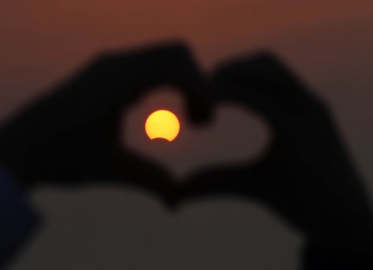 A Kuwaiti man makes the outline of a heart with his fingers to encompass a partially solar eclipse at Souq Sharq Marina in Kuwait City on November 3, 2013. A rare solar eclipse will sweep across parts of Africa, Europe and the United States as the moon blocks the sun either fully or partially, depending on the location. (Yasser Al-Zayvat/AFP Photo)