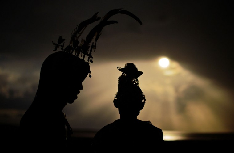 """Rendile tribe members are silhoutted after a rare solar eclipse in the Sibiloi national Park in Turkana on November 3, 2013. Astronomy enthusiasts in Kenya caught a partial glimpse of a rare """"Hybrid Total Eclipse"""" which hasn't been witnessed in Africa for over 40 years, though weather hampered a view of the complete eclipse. (Carlo Souza/AFP Photo)"""