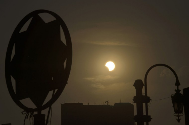 A partial solar eclipse is seen over the Egyptian capital Cairo, on November 3, 2013. The rare solar eclipse will sweep across parts of Africa, Europe and the United States as the moon blocks the sun either fully or partially, depending on the location. (Khaled Desoukiki/AFP Getty Photo)