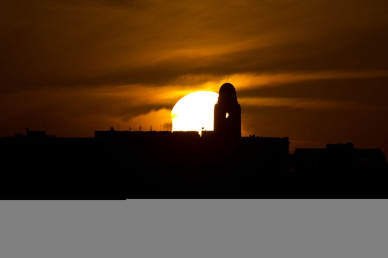 A partial solar eclipse is seen during sunset over the Jerusalem International YMCA in Jerusalem on November 3, 2013. The rare solar eclipse will sweep across parts of Africa, Europe and the United States as the moon blocks the sun either fully or partially, depending on the location. Menahem Kahana/AFP Photo)