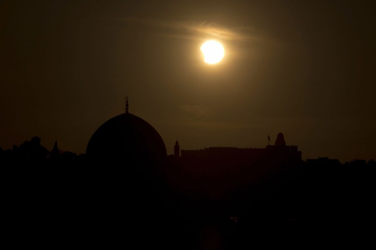 A partial eclipse is seen during sunset over the Dome of the Rock, a Muslim holy site, in Jerusalem's old city, on November 3, 2013. The rare solar eclipse will sweep across parts of Africa, Europe and the United States as the moon blocks the sun either fully or partially, depending on the location. (Menahem Kahana/AFP Photo)