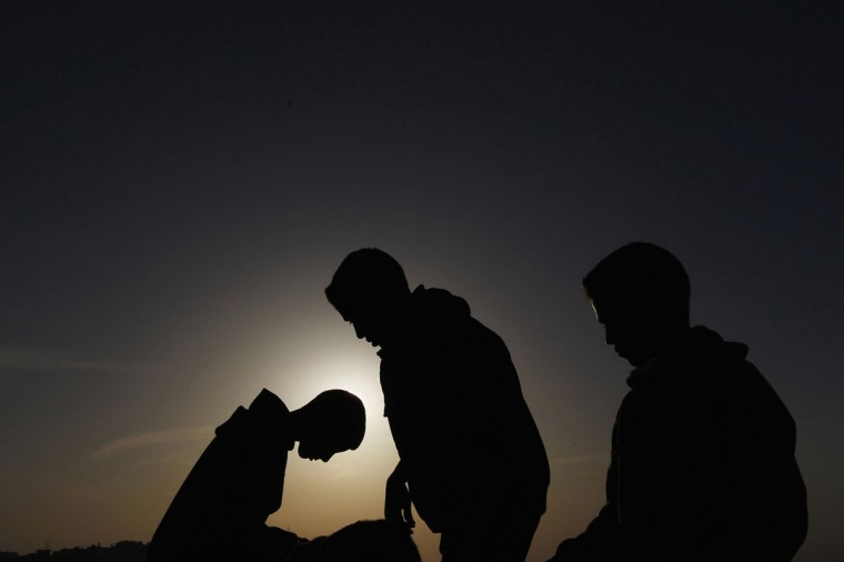 People observe a solar eclipse in Amman November 3, 2013. Sky watchers across the world are in for a treat Sunday as the final solar eclipse of 2013 takes on a rare hybrid form. (Muhammad Hamed/Reuters)