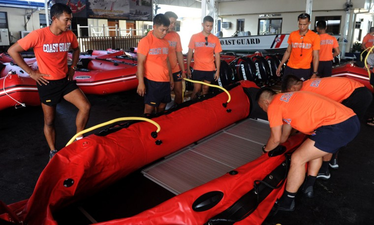 Philippine Coast Guard (PCG) personnel inflate newly-acquired rubber boats following a blessing ceremony in Manila on November 6, 2013. PCG Chief Rear Admiral Rodolfo Isorena ordered the newly-acquired rubber boats to be deployed to the central Philippines in preparation for the super typhoon Haiyan which is expected to make a landfall in that area on November 8. The Philippines is preparing for what it believes will be the most powerful typhoon to hit this storm-ravaged country this year. (Jay Directo/AFP Photo)