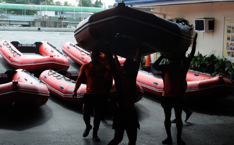 Philippine Coast Guard (PCG) personnel carry newly-acquired rubber boats following a blessing ceremony in Manila on November 6, 2013. PCG Chief Rear Admiral Rodolfo Isorena ordered the newly-acquired rubber boats to be deployed to the central Philippines in preparation for the super typhoon Haiyan which is expected to make a landfall in that area on November 8. The Philippines is preparing for what it believes will be the most powerful typhoon to hit this storm-ravaged country this year. (Jay Directo/AFP Photo)