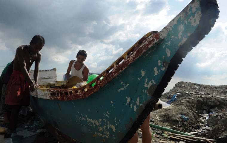 Fisherman repair there outrigger on the shore of Manila bay as Typhoon Haiyan approached on November 7, 2013. Authorities warned more than 12 million people were at risk from Typhoon Haiyan, which was generating wind gusts exceeding 330 kilometres (200 miles) an hour and set to hit on November 8. (Jay Directo/AFP Photo)