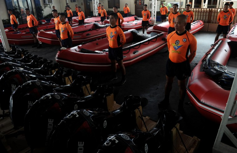 Philippine Coast Guard (PCG) personnel stand in formation beside newly-acquired rubber boats following a blessing ceremony in Manila on November 6, 2013. PCG Chief Rear Admiral Rodolfo Isorena ordered the newly-acquired rubber boats to be deployed to the central Philippines in preparation for the super typhoon Haiyan which is expected to make a landfall in that area on November 8. The Philippines is preparing for what it believes will be the most powerful typhoon to hit this storm-ravaged country this year. (Jay Directo/AFP Getty Images)