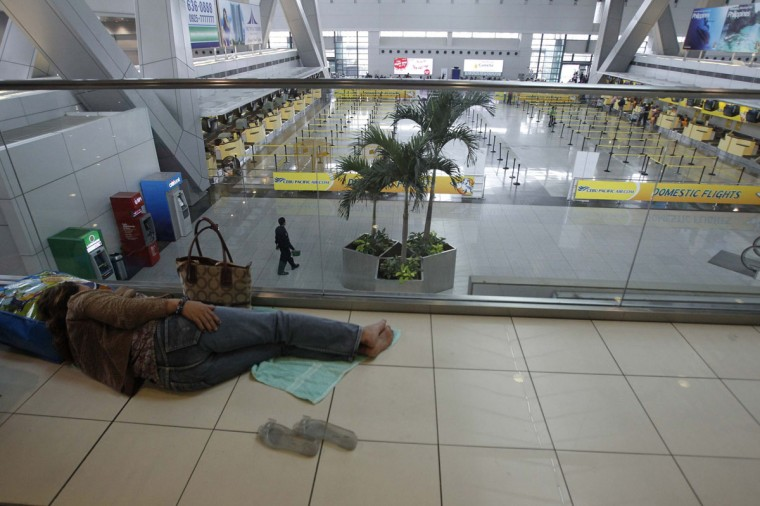A stranded passenger lies on the floor inside Ninoy Aquino International airport in Pasay city, metro Manila November 8, 2013, after nearly 200 local flights have been suspended due to Typhoon Haiyan that hit central Philippines. Typhoon Haiyan, the strongest storm on earth this year, slammed into the Philippines' central islands on Friday forcing millions of people to move to safer ground and storm shelters, cutting power and phone lines, and grounding air and sea transport. (Romeo Ranoco/Reuters)