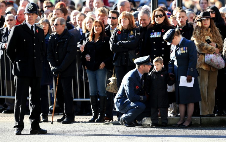 Wg Cdr Chris Brown, Sqn Ldr Laura Brown, (far right) who are both serving with the RAF and their son Harrison, watch as service personnel, members of the armed forces and other veterans attend a Remembrance Day ceremony on November 10, 2013 in Bristol, England. People across the UK gathered to pay tribute to service personnel who have died in the two World Wars and subsequent conflicts, as part of the annual Remembrance Sunday ceremonies. (Matt Cardy/Getty Images)
