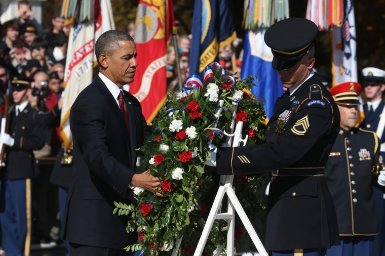U.S. President Barack Obama (L) positions a commemorative wreath during a ceremony on Veterans Day at the Tomb of the Unknowns at Arlington National Cemetery on November 11, 2013 in Arlington, Virginia. For Veterans Day, President Obama is paying tribute to military veterans past and present who have served and sacrificed their lives for their country. (Mark Wilson/Getty Images)
