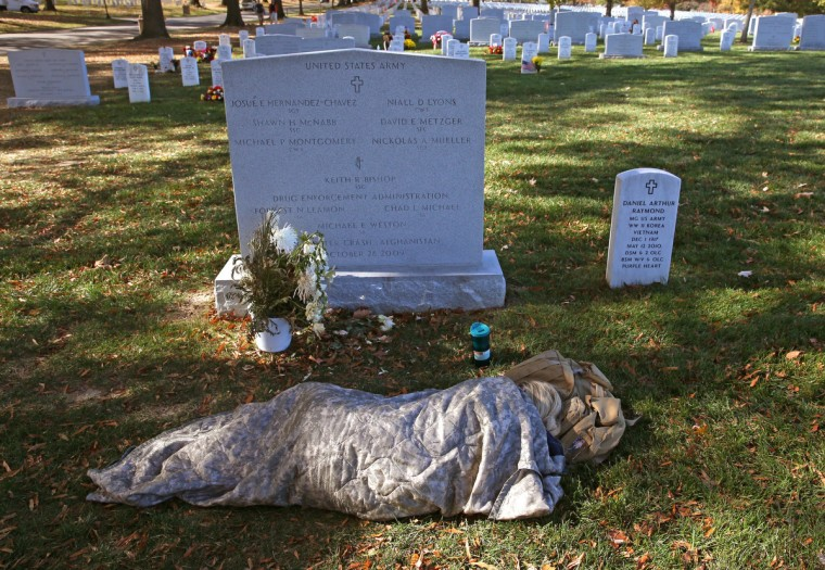 Sarah Stancyzk lays covered up at the gravesite of her husband Pfc. David Metzger who was killed in Afghanistan in 2009, at Section 60 in Arlington Cemetery, November 11, 2013 in Arlington, Virginia. For Veterans Day, President Obama laid a wreath at the Tomb Of Unknowns to pay tribute to military veterans past and present who have served and sacrificed their lives for their country. (Mark Wilson/Getty Images)