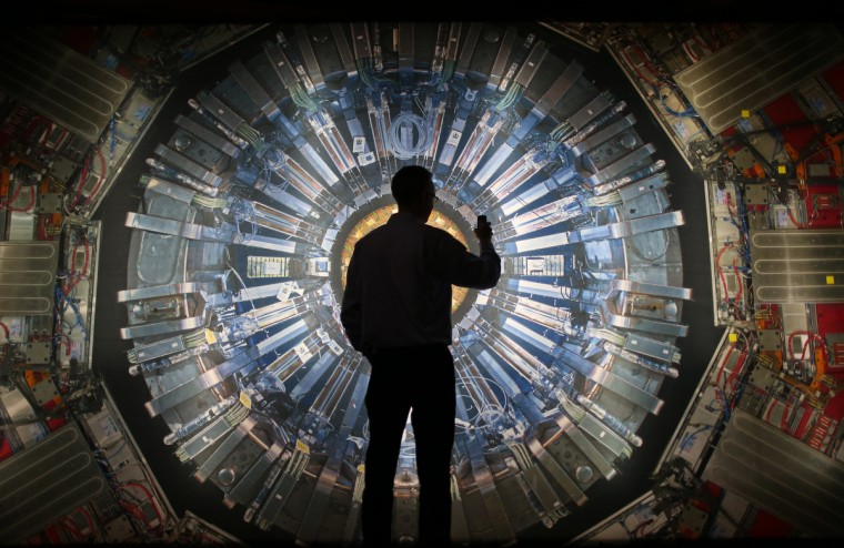 A visitor takes a phone photograph of a large back lit image of the Large Hadron Collider (LHC) at the Science Museum's 'Collider' exhibition in London, England. At the exhibition, which opens to the public on November 13, 2013 visitors will see a theatre, video and sound art installation and artifacts from the LHC, providing a behind-the-scenes look at the CERN particle physics laboratory in Geneva. It touches on the discovery of the Higgs boson, or God particle, the realization of scientist Peter Higgs theory. (Peter Macdiarmid/Getty Images)
