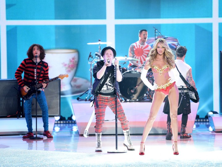 Musicians Joe Trohman, Patrick Stump, Andy Hurley, and Pete Wentz of the band Fall Out Boy perform and model Candice Swanepoel, wearing the Royal Fantasy Bra and Belt, walks the runway at the 2013 Victoria's Secret Fashion Show at Lexington Avenue Armory on November 13, 2013 in New York City. (Dimitrios Kambouris/Getty Images)