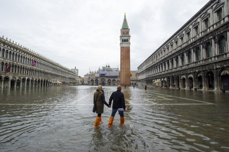 A couple walks in a flooded Saint Mark's Square during high waters in Venice, Italy. Venice will be affected by the high water for the next few days due to the passage of Cyclone Cleopatra that hit the Italian island of Sardinia causing devastating flooding, which has left at least 17 dead. (Marco Secchi/Getty Images)