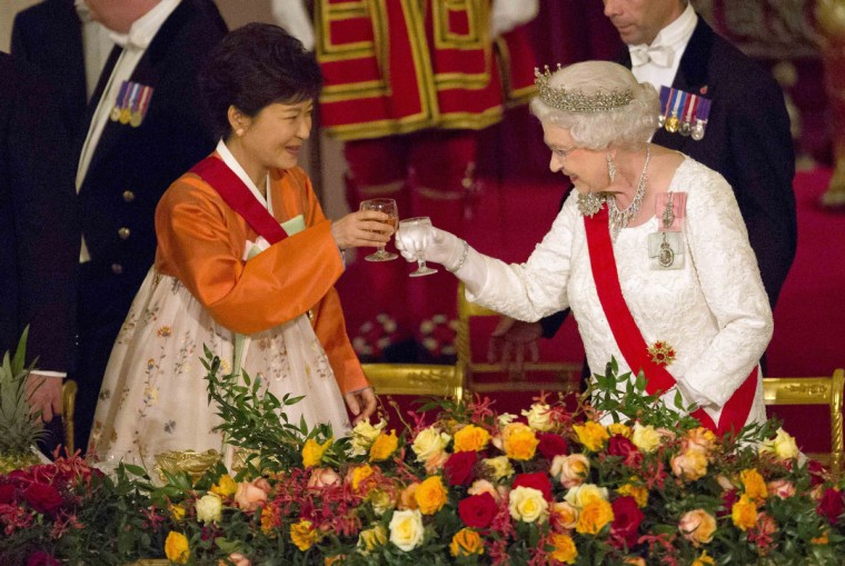 Britain's Queen Elizabeth II (R) and South Korea's President Park Geun-Hye (L) raise a toast at a State Banquet at Buckingham Palace in London. South Korea's President Park Geun-Hye was treated to a full display of British pomp and ceremony as she began a three-day state visit to London. Queen Elizabeth II and her husband Prince Philip accompanied Park in a horse-drawn carriage as they rode to Buckingham Palace, while troops welcomed her with a 41-gun salute at Green Park and the Tower of London. (Neil Hall/Getty Images)
