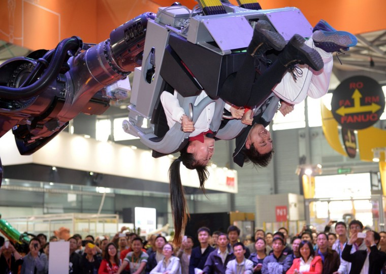"""Visitors ride in a robot arm called """"ROBOcoaster"""" at the China International Industry Fair 2013 in Shanghai. Chinese manufacturing grew at its strongest pace in 18 months in October, figures showed recently, but government and independent analysts warned underlying data suggest economic weaknesses remain. (Peter Parks/Getty Images)"""