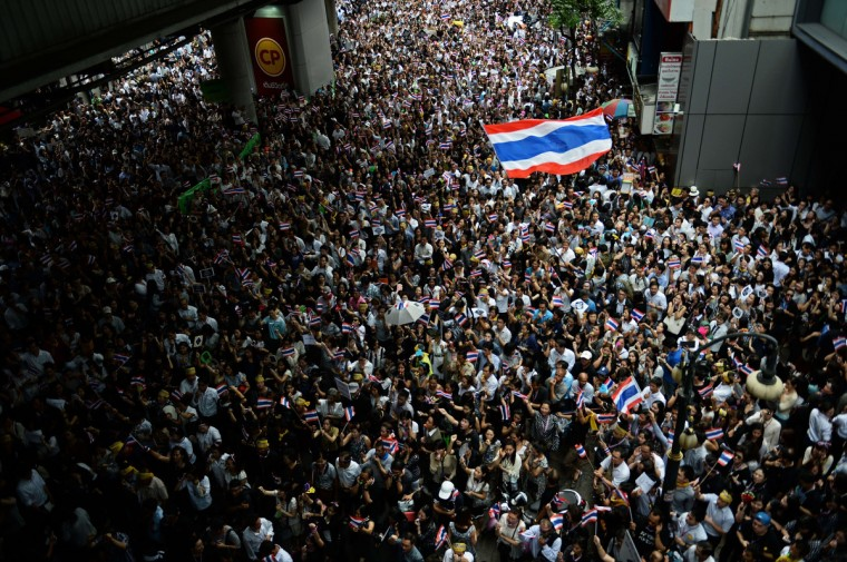 "Thai opposition protesters wave national flags during a rally against a controversial political amnesty bill that has sparked mass anti-government protests, urging the country to ""forgive"" after years of civil strife, in Bangkok's financial district of Silom on November 6, 2013. Thousands of anti-government protesters have been gathering daily in Bangkok since lawmakers approved a controversial amnesty that could allow fugitive former prime minister Thaksin Shinawatra to return. (Christophe Archambault/Getty Images)"
